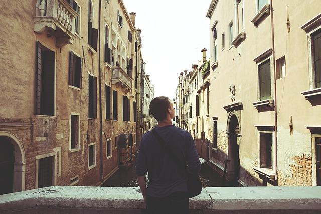 Chlapec v historickom meste, sfotený zozadu s crossbody taškou