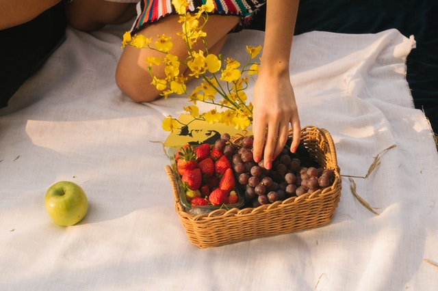 Žena kľačí na kolenách a vyberá ovocie z prúteného košíka