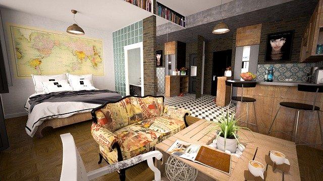 Miestnosť s posteľou, kuchynským stolom a kuchyňou.jpg