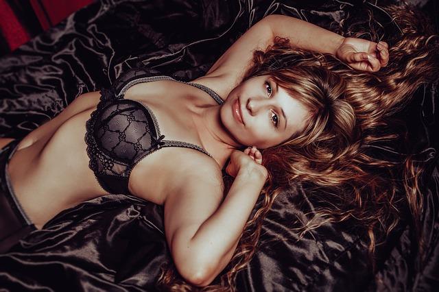 Žena v čiernej podprsenke leží na hodvábnej deke na posteli